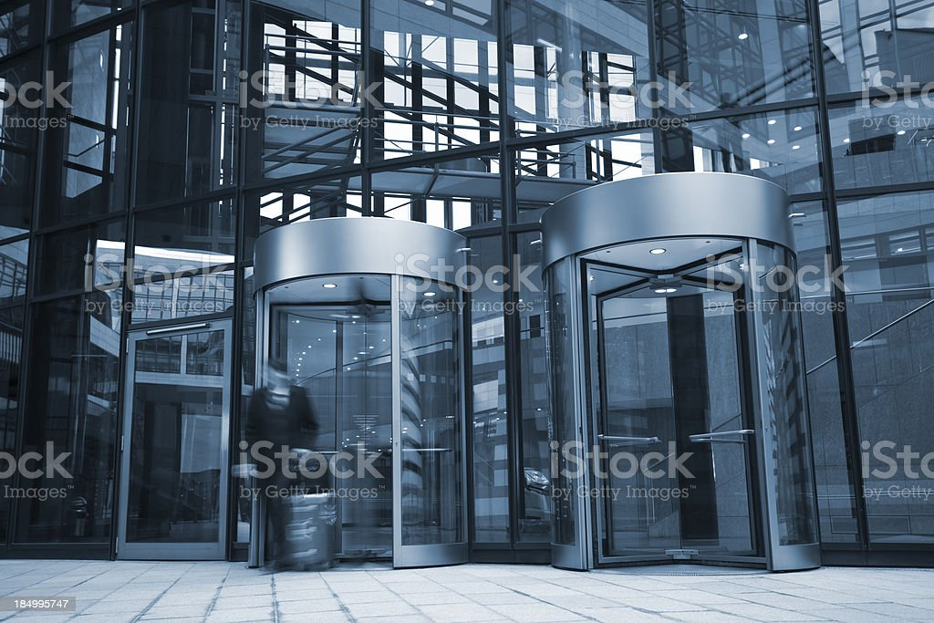 Businessman Exiting Office Building Through Revolving Door stock photo