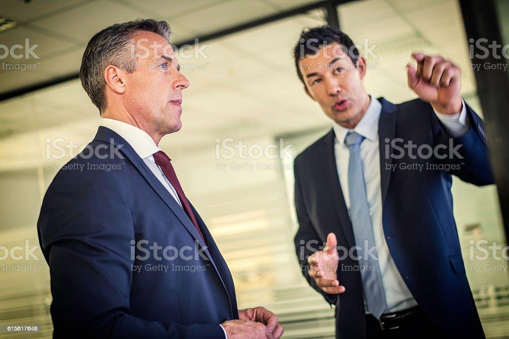 Businessman explaining something to his boss stock photo