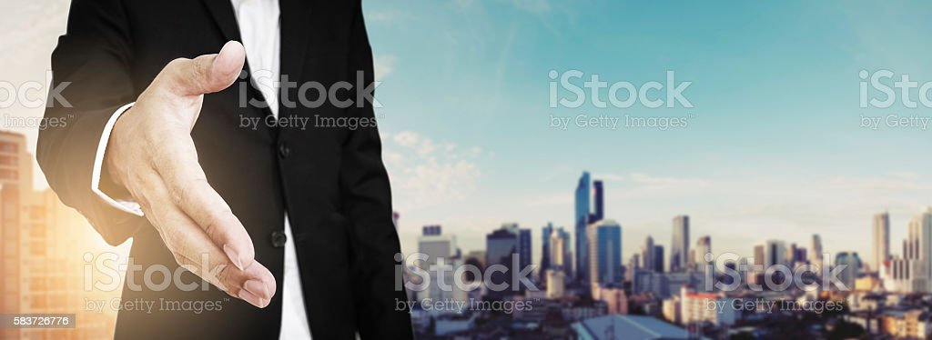 Businessman extending hand with panoramic cityscape in sunrise, vintage tone stock photo