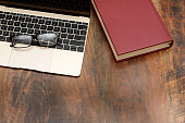 Businessman Eyeglasses and Red Book on Wood Table