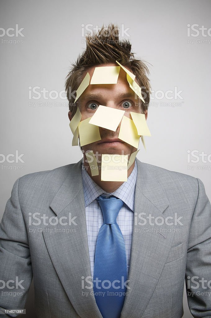 Businessman Face Covered in Yellow Sticky Notes Looking at Camera stock photo