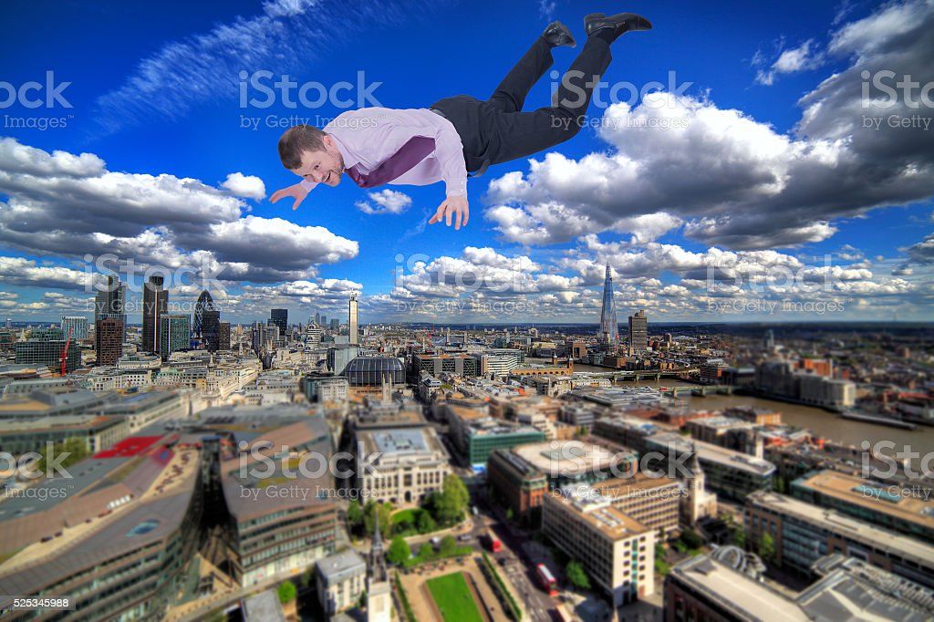 Businessman falling down with modern city in background stock photo