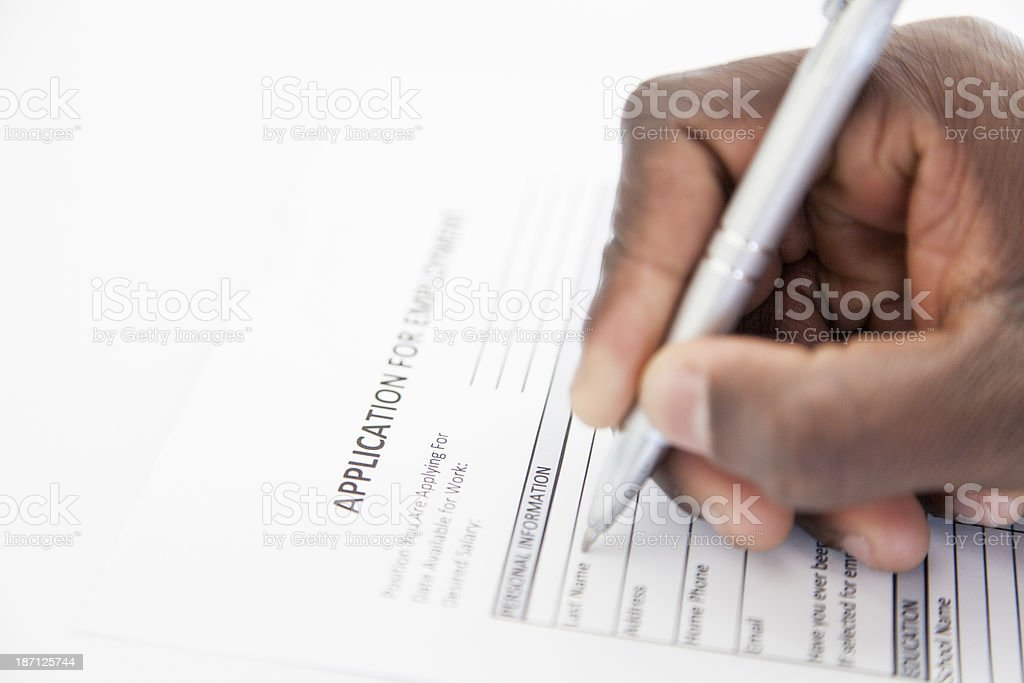 Businessman filling in an application form in pen stock photo