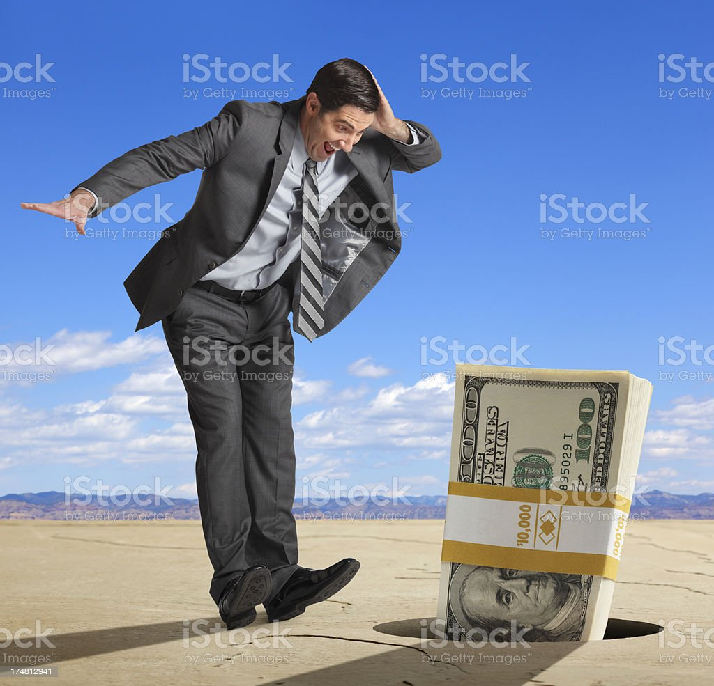 Businessman finds stack of one hundred dollar bills in hole stock photo