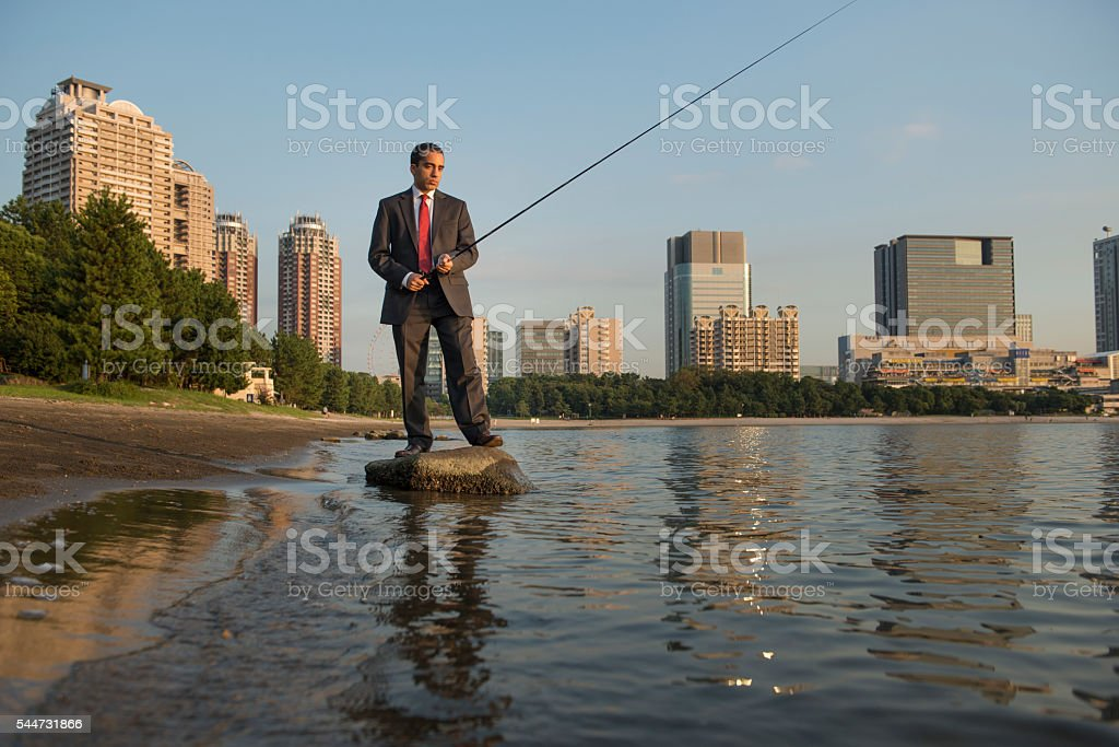 Businessman fishing in the city. stock photo