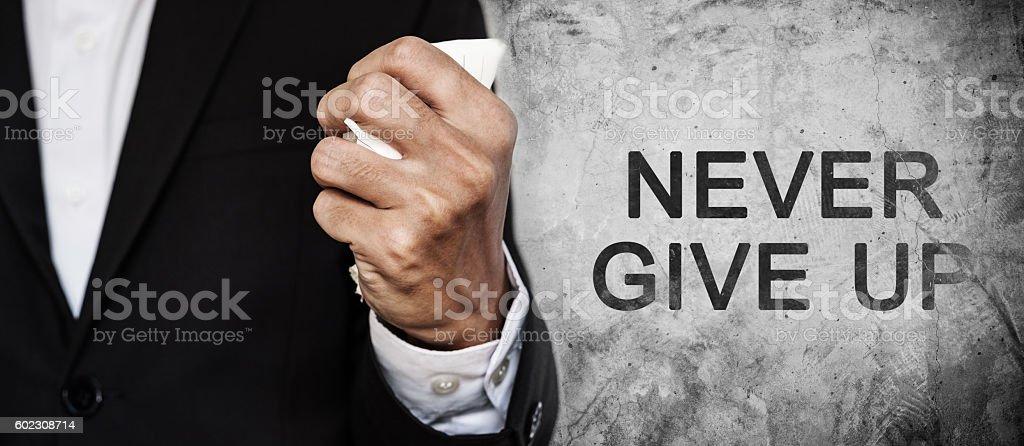Businessman fist squeeze paper on concrete texture stock photo