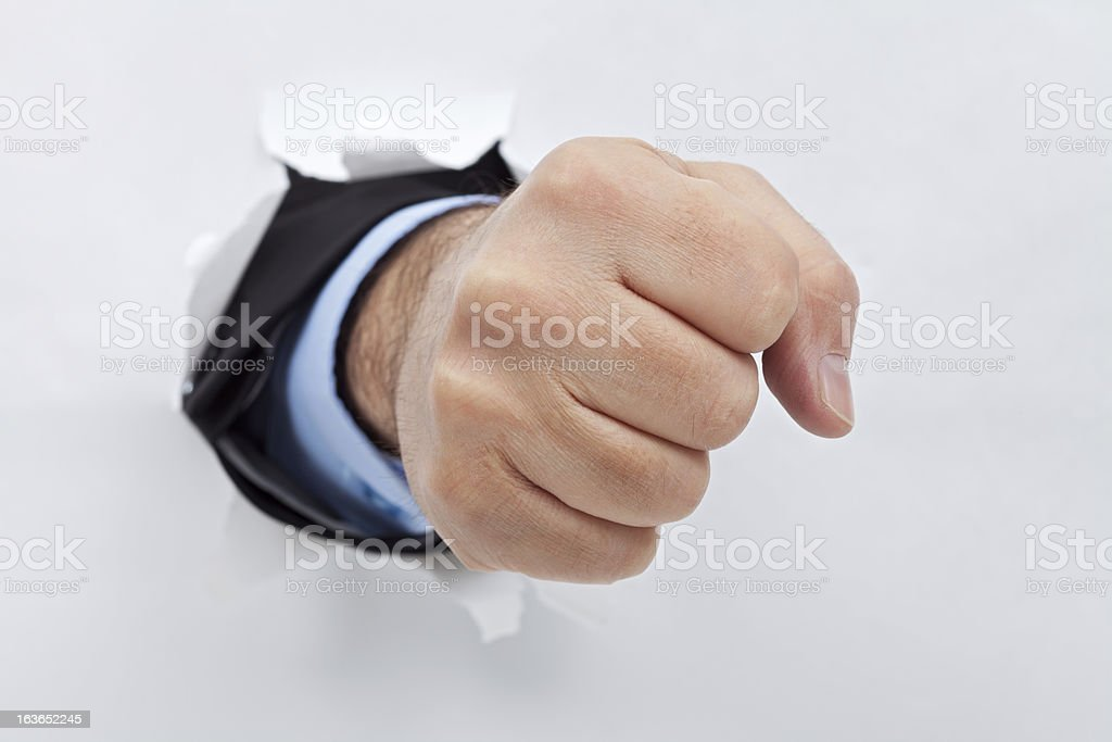 Businessman fist through the paper royalty-free stock photo