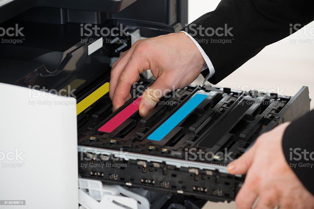 Businessman Fixing Cartridge In Photocopy Machine stock photo