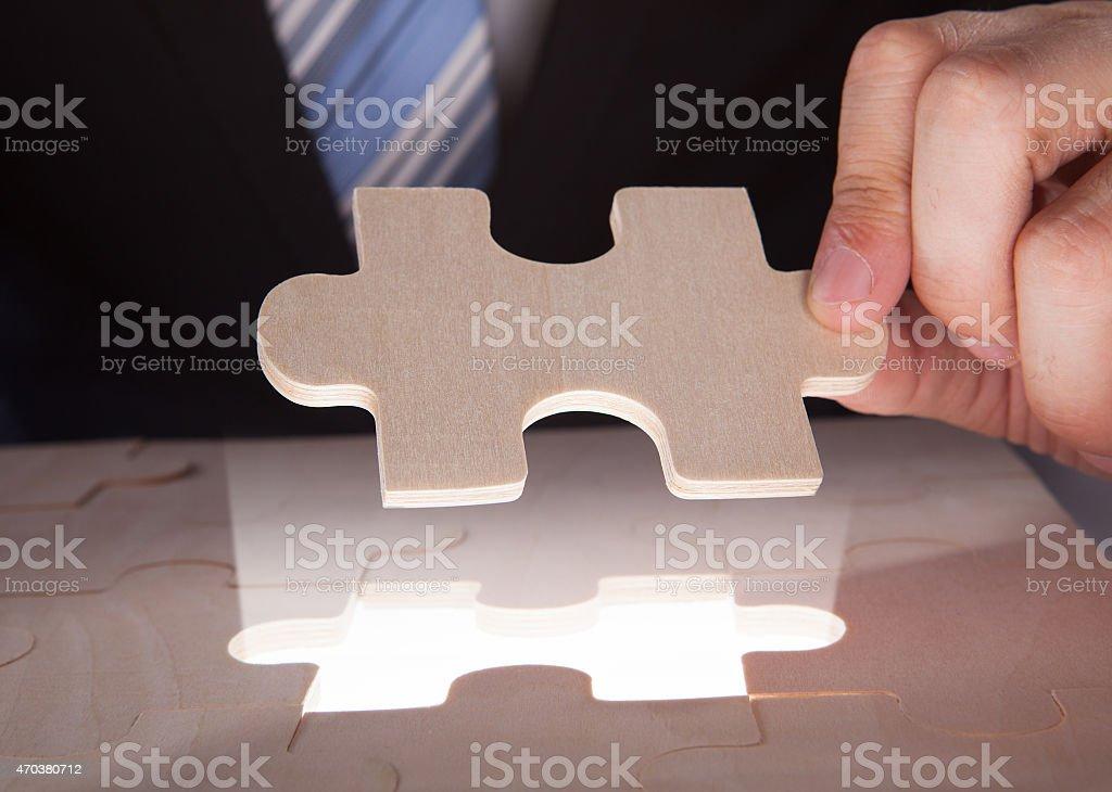 Businessman Fixing Jigsaw Pieces At Desk stock photo