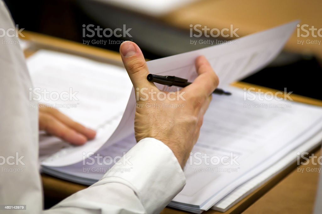 Businessman flipping business papers on a wooden desk stock photo