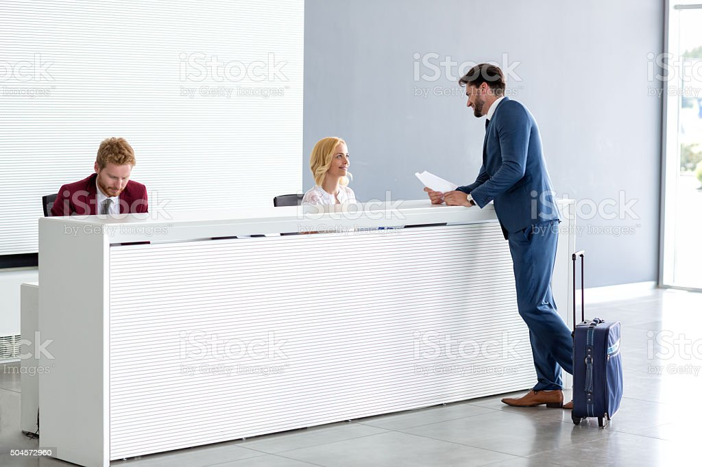 Businessman flirting at reception with female receptionist stock photo