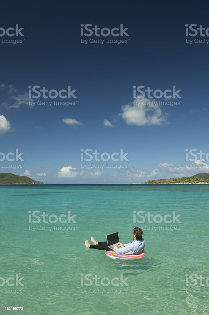 Businessman Floating Typing on Laptop in Tropical Bay royalty-free stock photo