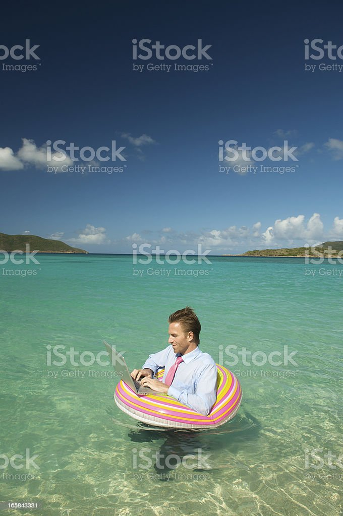 Businessman Floats in Tropical Waters with Laptop royalty-free stock photo