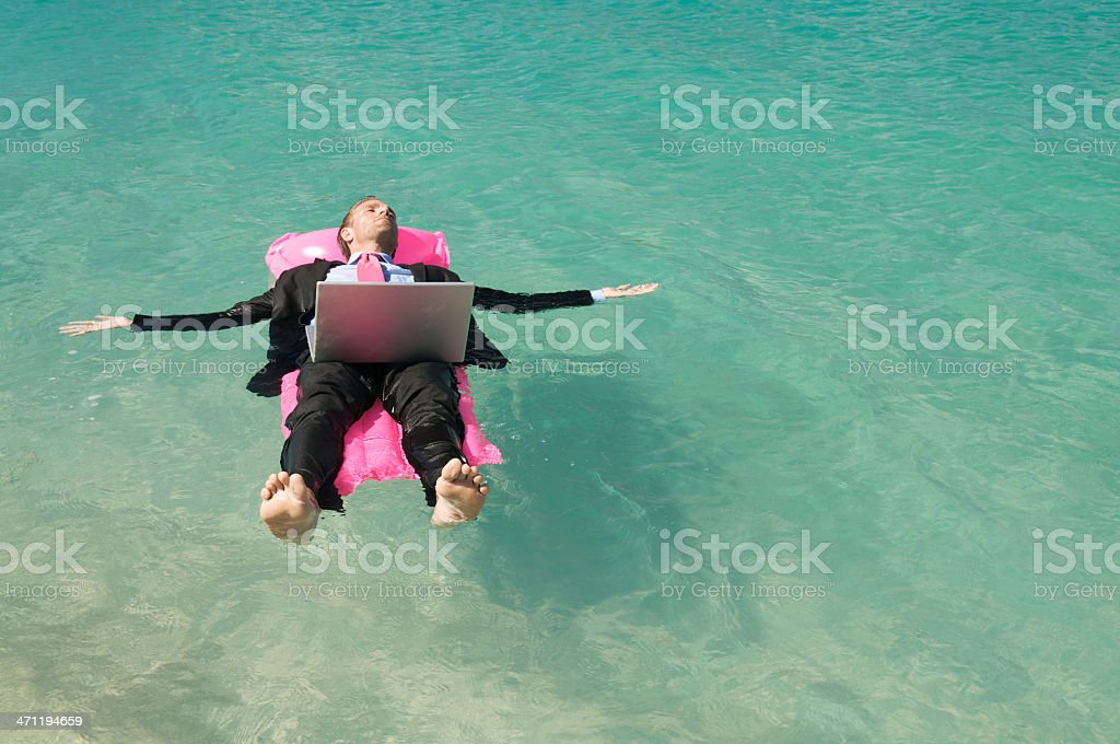 Businessman Floats on Pink Lilo with Laptop royalty-free stock photo