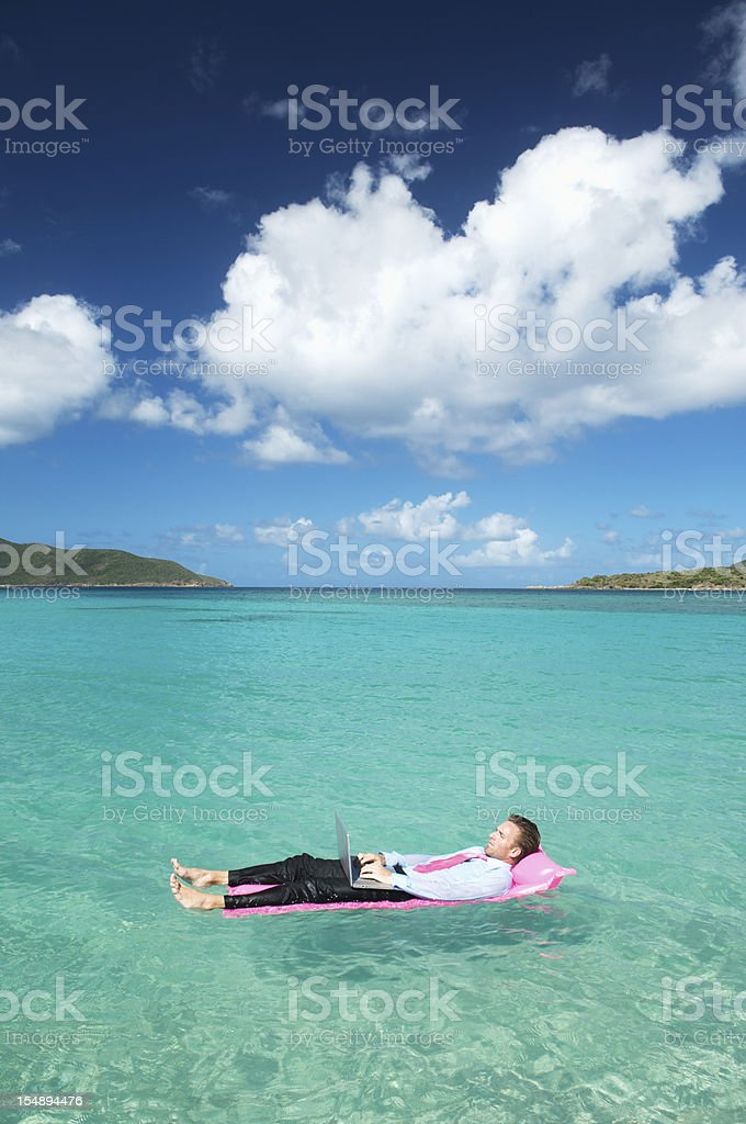 Businessman Floats with Laptop on Tropical Bay royalty-free stock photo