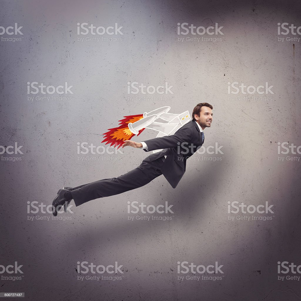 Businessman flying with rocket backpack stock photo