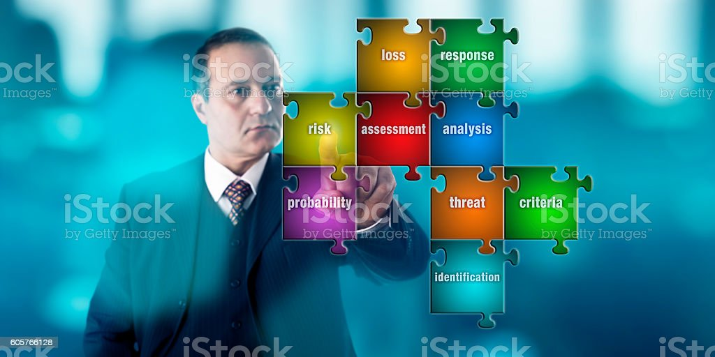 Businessman Focussing On A Risk Assessment Puzzle stock photo