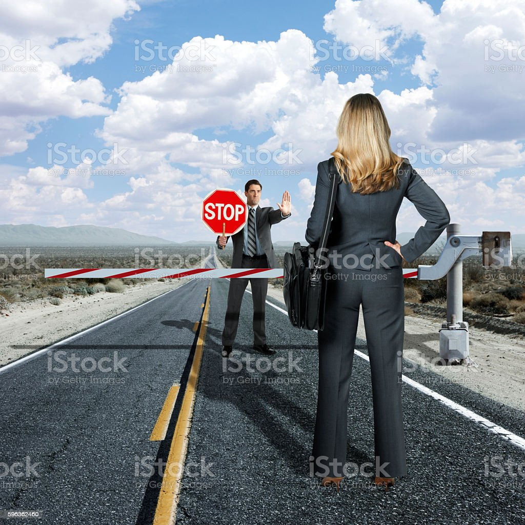 Businessman Forbidding Businesswoman From Moving On stock photo
