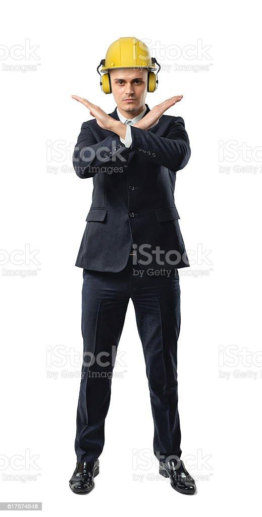Businessman full height wearing yellow helmet with earphones, giving forbidding stock photo