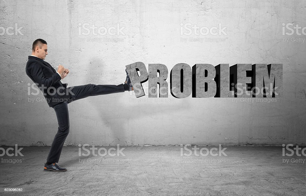 Businessman full-height in profile, kicking a big word 'PROBLEM' stock photo