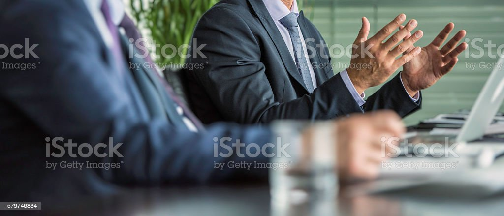 Businessman gesturing with hands at a board meeting stock photo