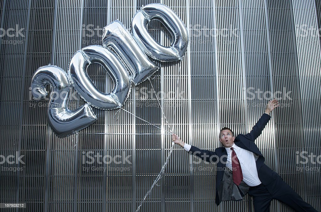 Businessman Gets Carried Away By 2010 Balloons royalty-free stock photo