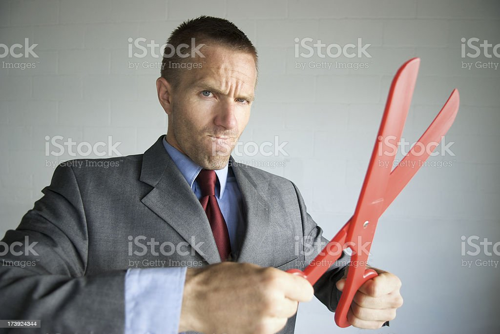 Businessman Gets Serious about Cutting Costs with Red Scissors royalty-free stock photo