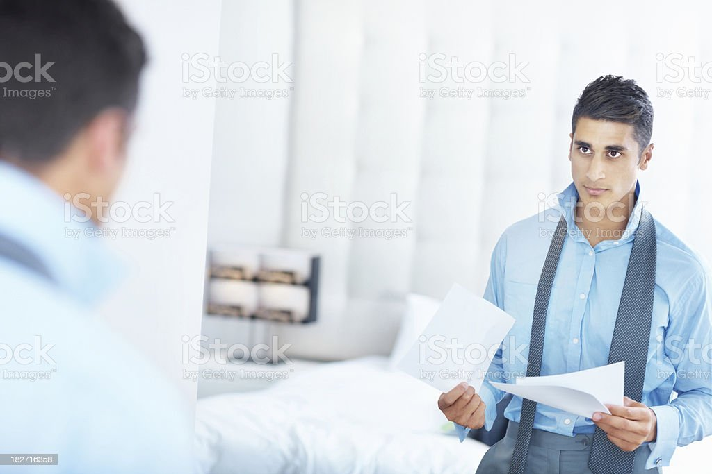 Businessman getting dressed for the office and holding documents stock photo