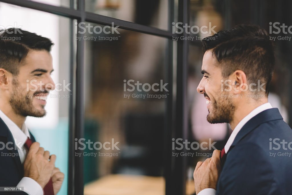 Businessman getting dressed in front of the mirror stock photo
