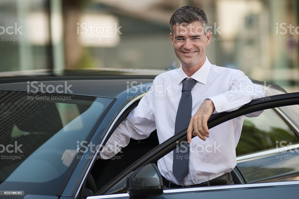 Businessman getting in his car stock photo