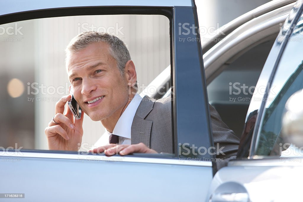 Businessman getting out of car talking with cell phone stock photo