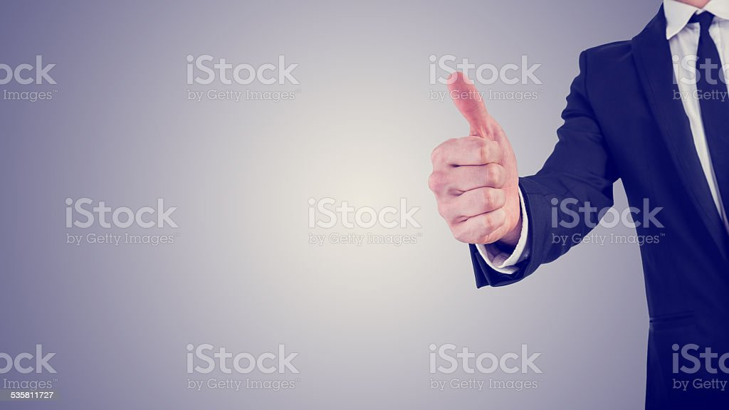 Businessman giving a thumbs up gesture in a business motivation stock photo