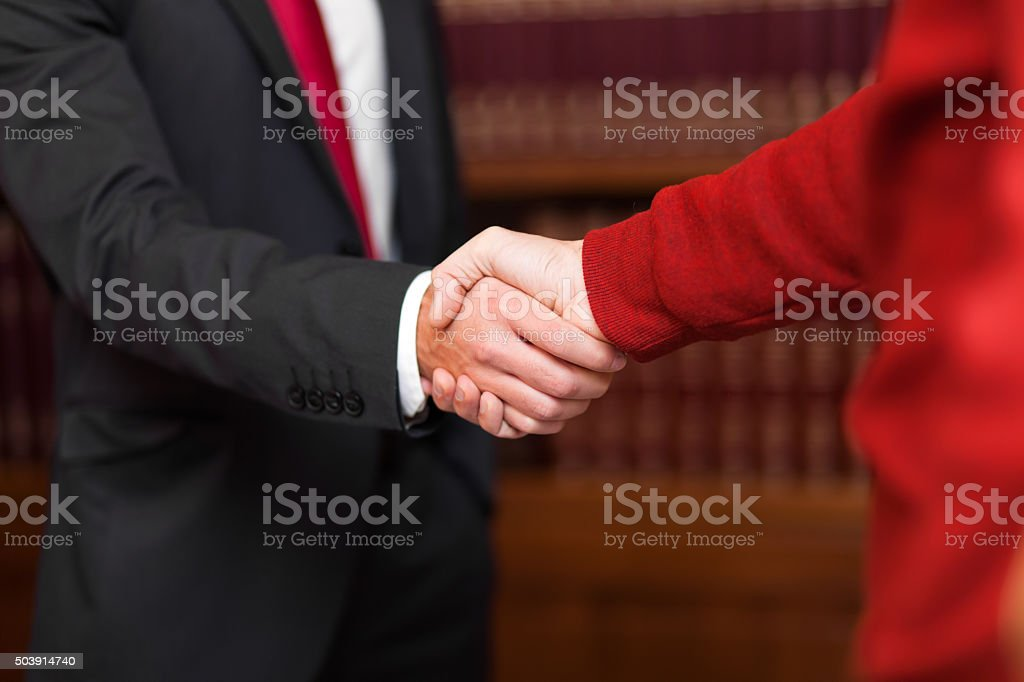 Businessman giving an handshake to a customer stock photo
