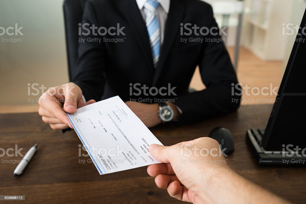 Businessman Giving Cheque To Other Person stock photo