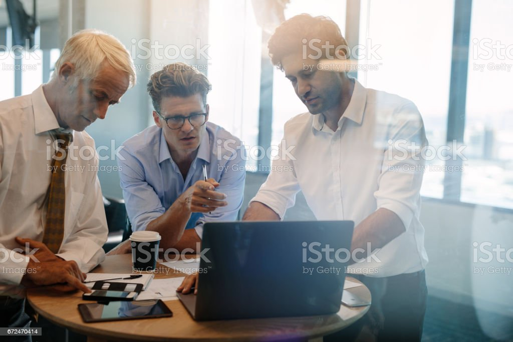 Businessman giving demonstrating on laptop to colleagues stock photo