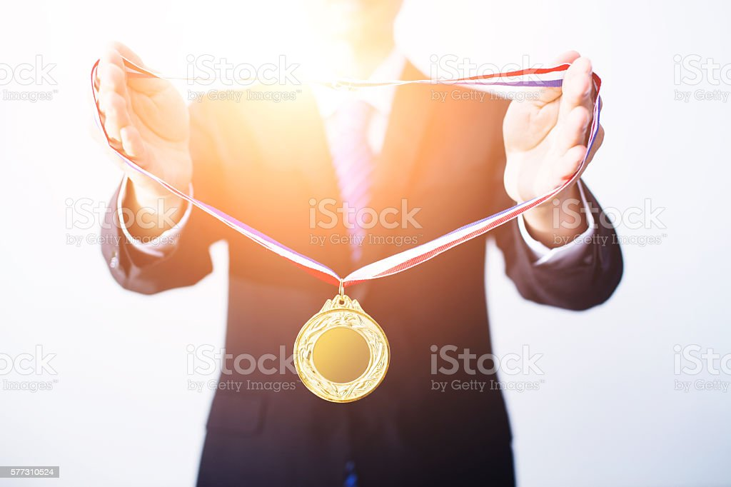 Businessman giving gold medal stock photo