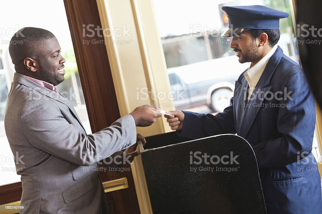 Businessman giving hotel valet ticket to retrieve his car stock photo