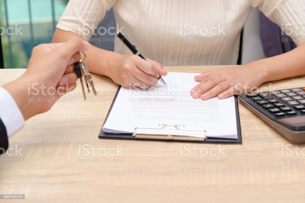 Businessman giving key and customer signing loan agreement document with calculator on wooden desk. stock photo