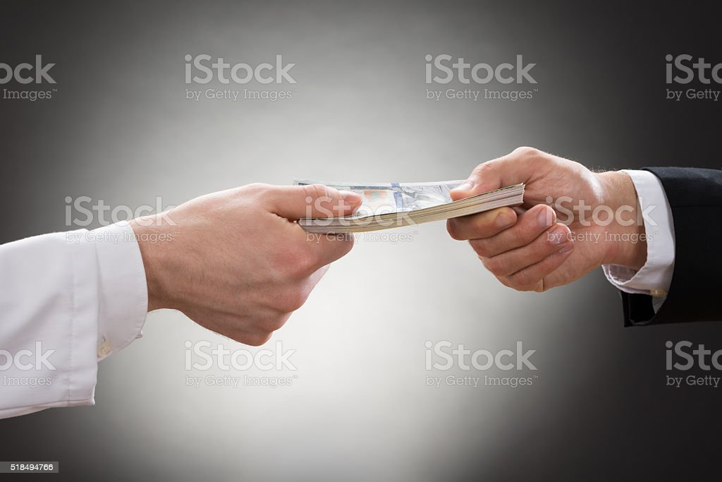 Businessman Giving Money To Doctor stock photo
