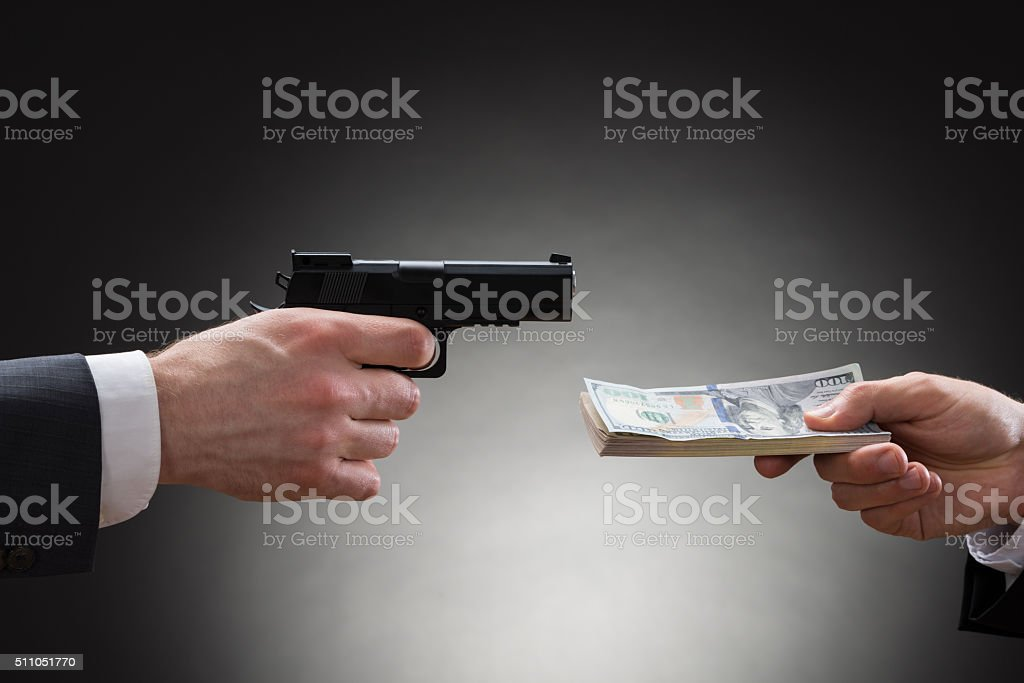 Businessman Giving Money To The Businessperson With Gun stock photo