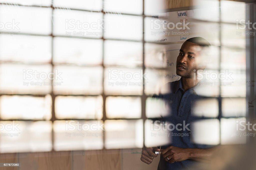 Businessman giving presentation seen through glass stock photo