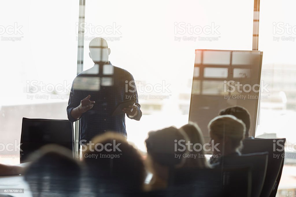 Businessman giving presentation to colleagues stock photo