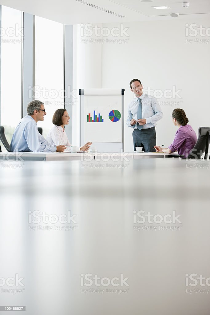 Businessman giving presentation to his colleagues at conference room royalty-free stock photo