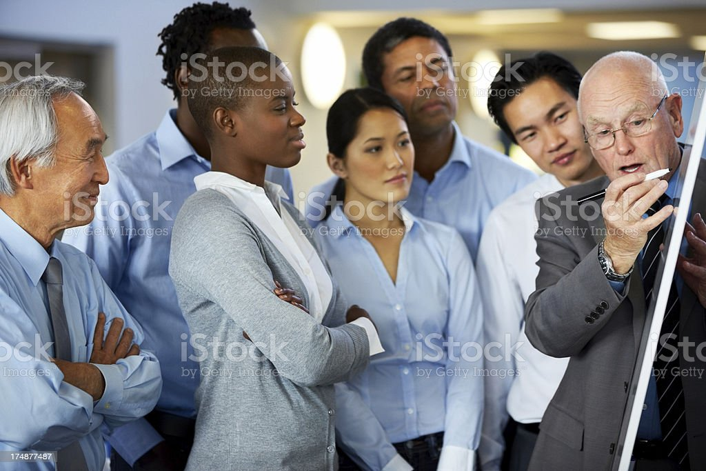 Businessman giving presentation to his team stock photo