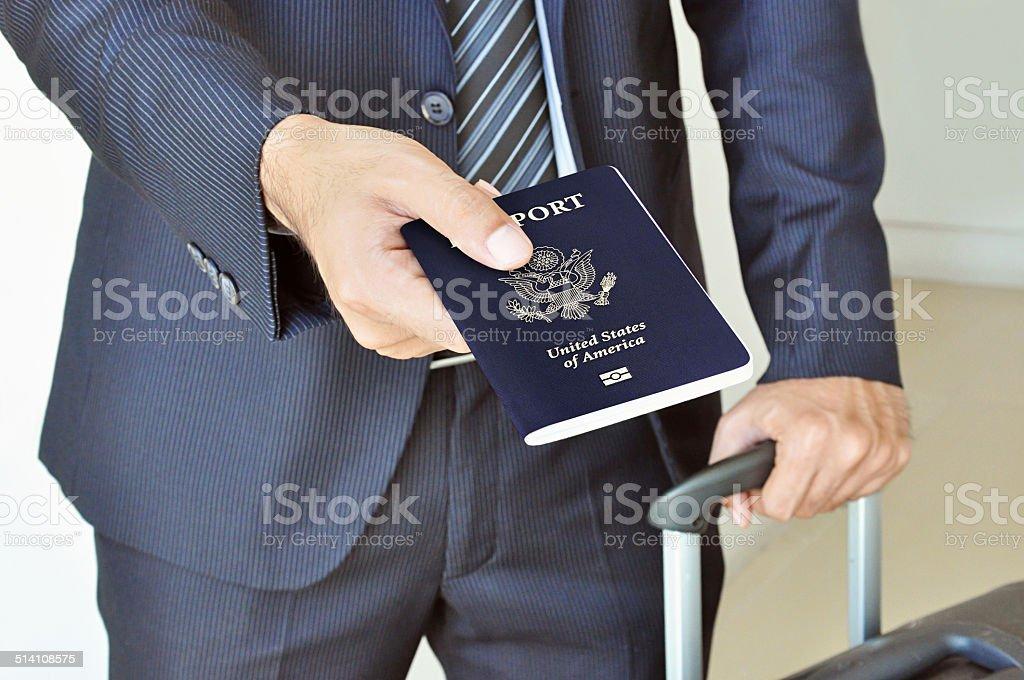 Businessman giving U.S. passport stock photo