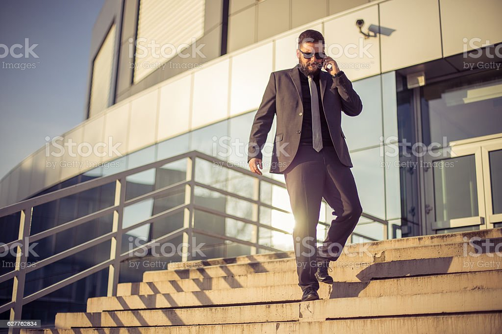 Businessman going down stairs and talking on phone stock photo