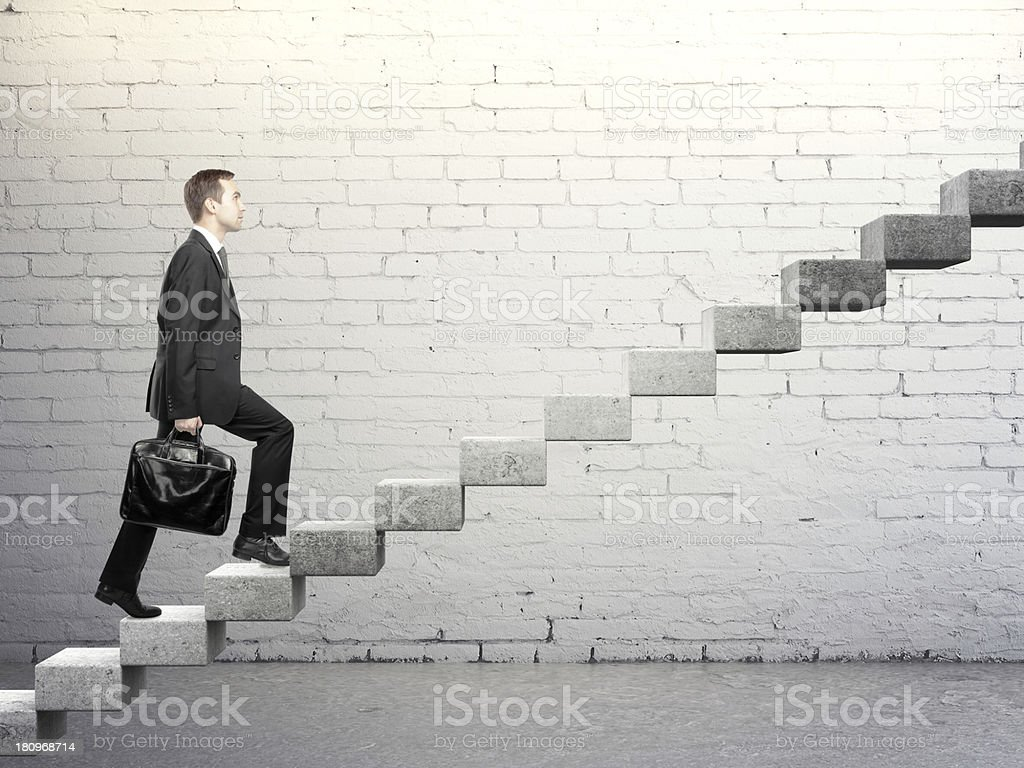 Businessman going up a concrete ladder with steady pace royalty-free stock photo