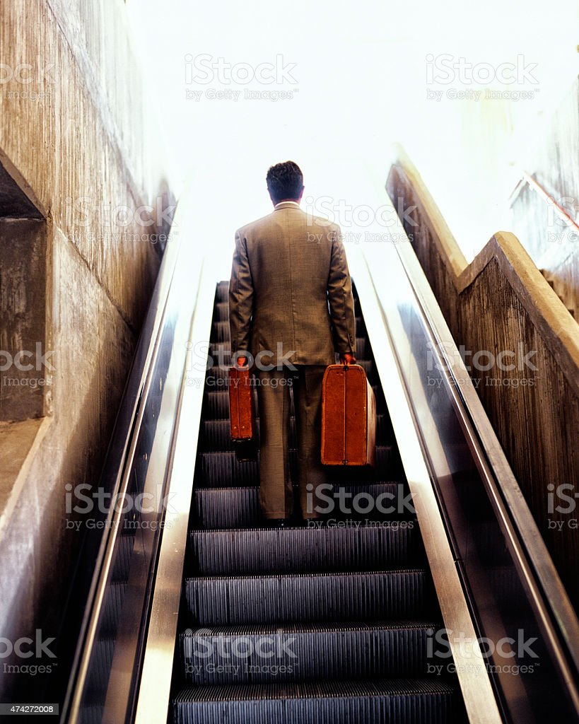 Businessman going up escalator with luggage. stock photo