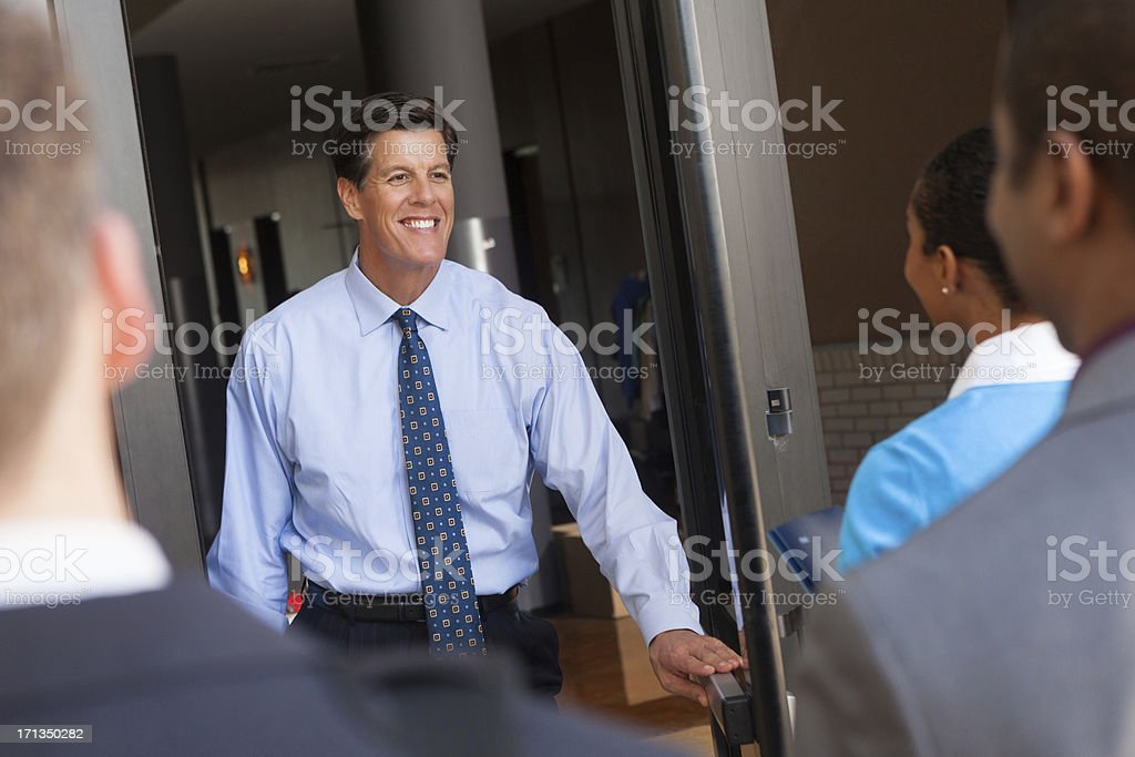 Businessman greeting employees moving in to new office building stock photo
