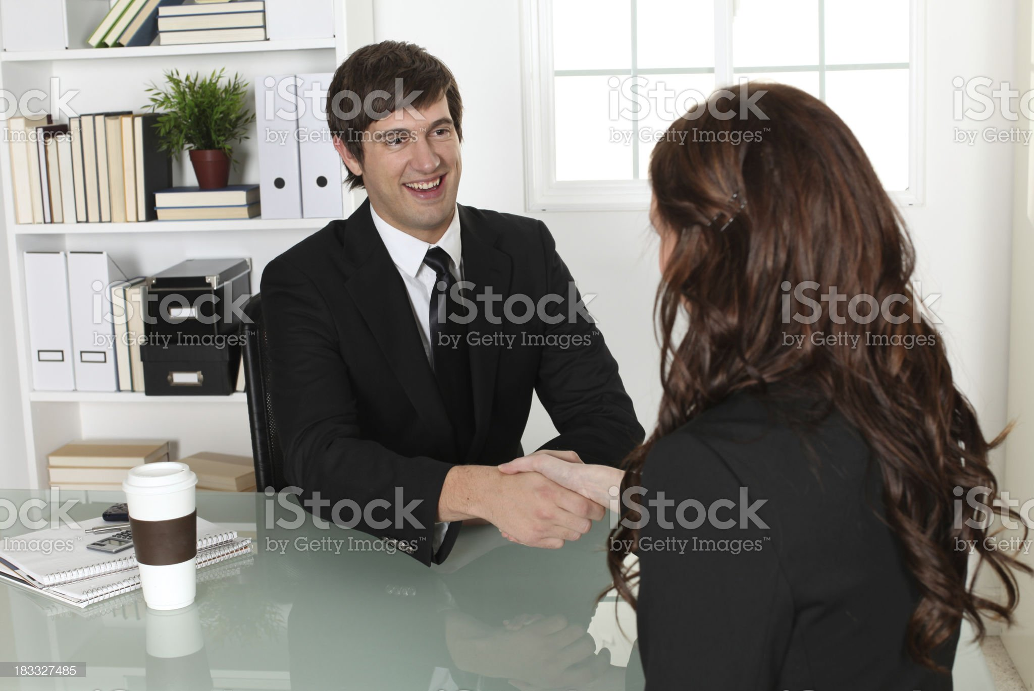 Businessman greeting woman sitting behind desk royalty-free stock photo